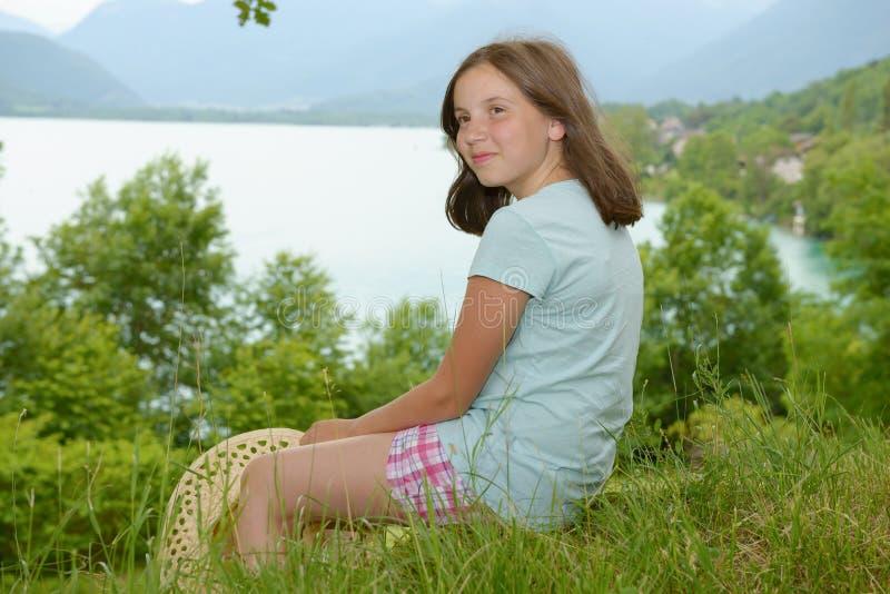 Ragazza abbastanza pre teenager che si siede nell'erba fotografia stock libera da diritti