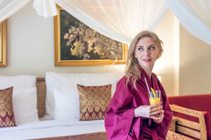 Ragazza abbastanza sexy del ritratto sul letto in appartamento moderno di mattina con il succo del mango Isola di Bali, villa Don immagini stock libere da diritti