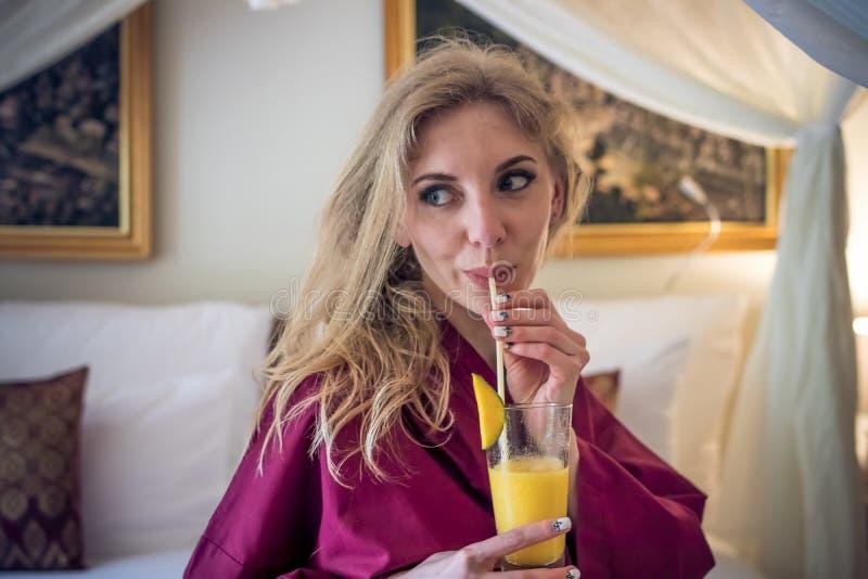 Ragazza abbastanza sexy del ritratto sul letto in appartamento moderno di mattina con il succo del mango Isola di Bali, villa Don fotografie stock libere da diritti