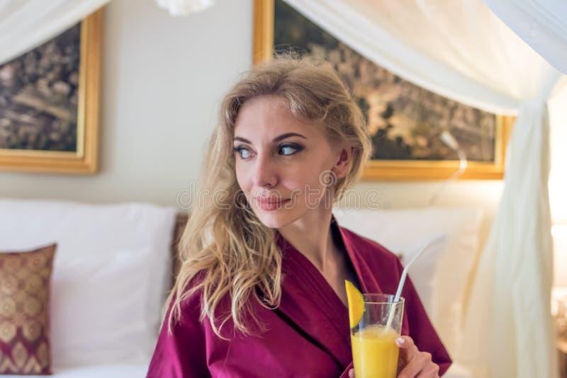 Ragazza abbastanza sexy del ritratto sul letto in appartamento moderno di mattina con il succo del mango Isola di Bali, villa Don fotografia stock