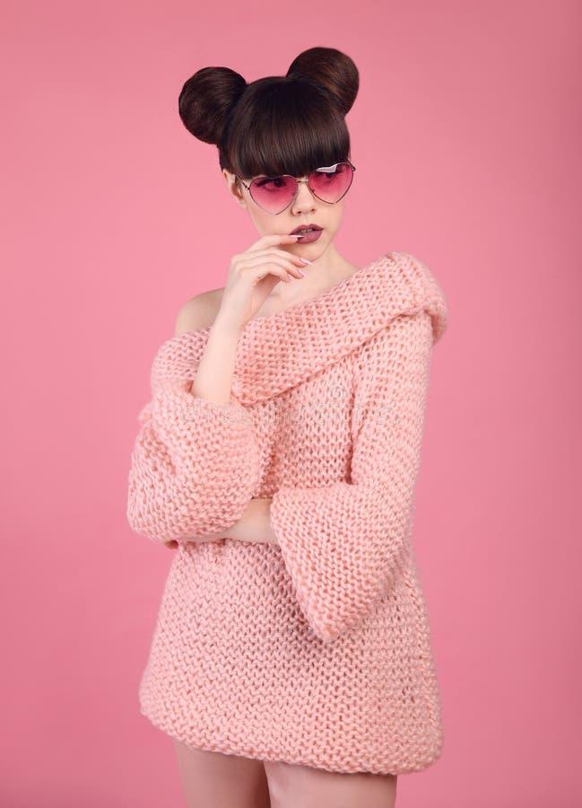 Ragazza abbastanza teenager in maglione tricottato sopra fondo rosa Fashio fotografia stock libera da diritti