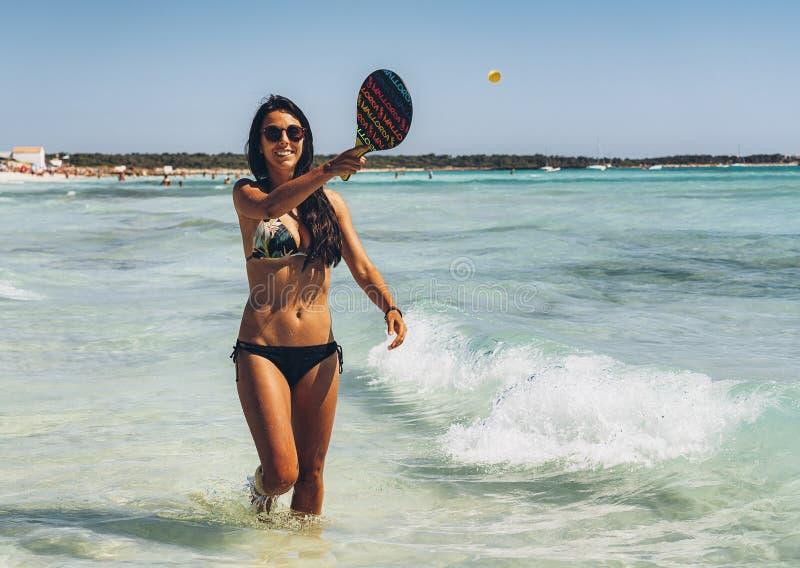 Ragazza abbronzata che gioca a tennis in una spiaggia di paradiso immagini stock