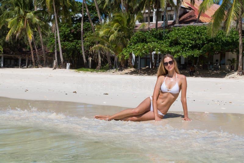 Ragazza abbronzata sexy in costume da bagno bianco che posa sulla spiaggia sabbiosa Il bello modello prende il sole e riposa sull fotografia stock