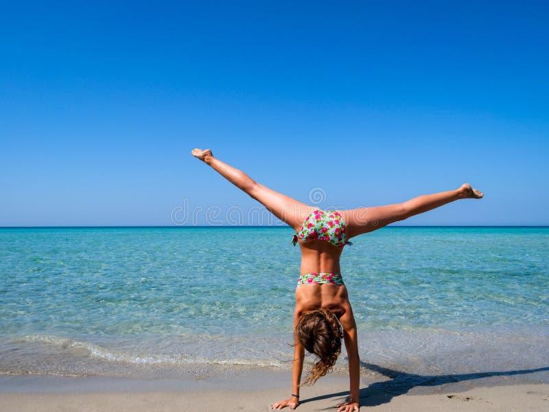Ragazza abbronzata sportiva che fa un cartwheel su una spiaggia meravigliosa con relativo alla ginnastica acqua del turchese fotografia stock