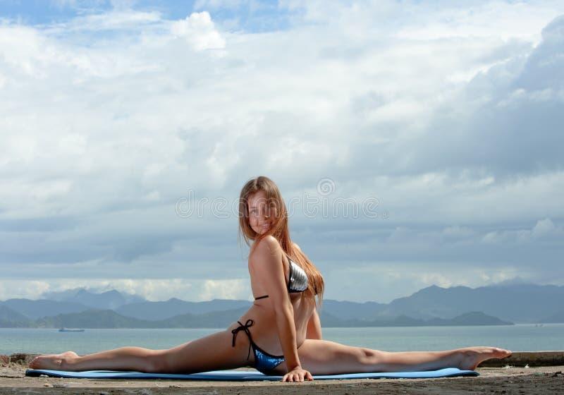 Ragazza acrobatica sulla spiaggia. immagine stock