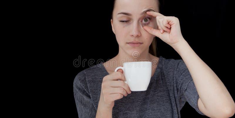 Ragazza addormentata calda della bevanda A che tiene una tazza di tè o di caffè su un fondo nero fotografie stock
