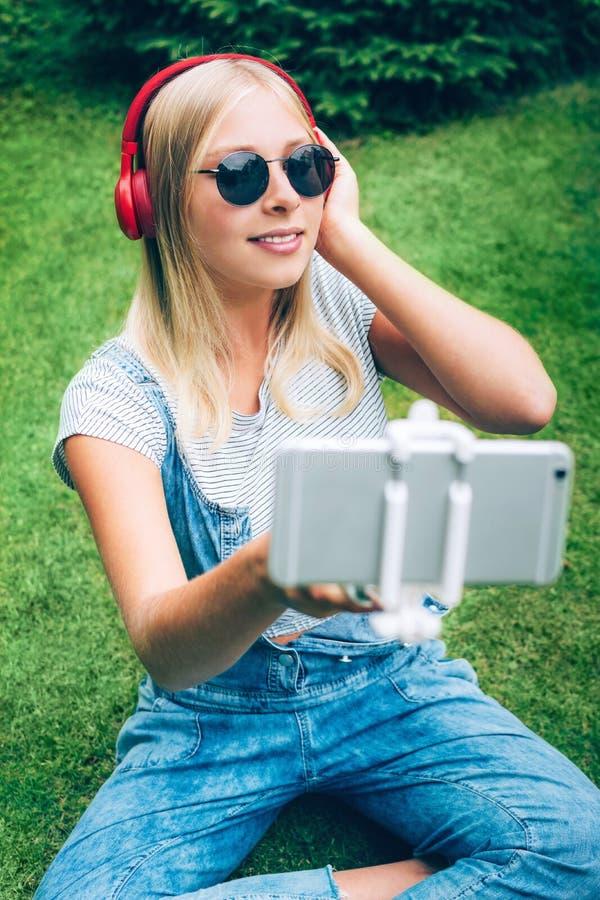 Ragazza adolescente con le cuffie rosse che si fa selfie su sfondo naturale verde fotografia stock