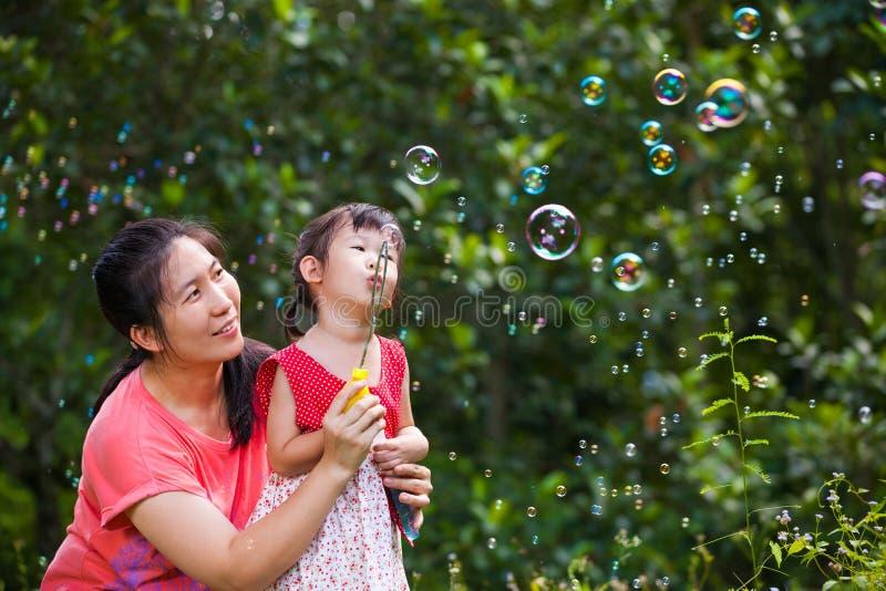 Ragazza adorabile asiatica e le sue bolle di sapone di salto della madre Famiglia dentro fotografie stock