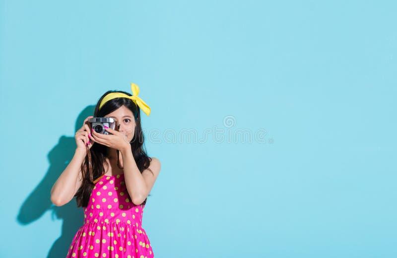 Ragazza adorabile attraente che usando la macchina fotografica d'annata di stile fotografia stock libera da diritti