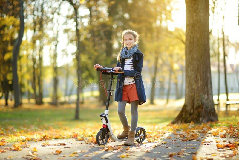 Ragazza adorabile che guida il suo motorino in un parco della città sulla sera soleggiata di autunno Bambino preteen grazioso che fotografia stock