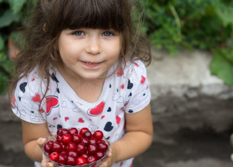 Ragazza adorabile con le ciliege fresche delle bacche nel giardino fotografie stock libere da diritti