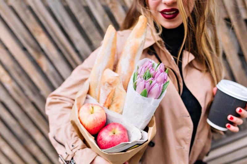 Ragazza adorabile con le labbra rosse che giudicano una borsa, i fiori ed il cappuccino di drogheria isolati sul fondo di legno d fotografia stock