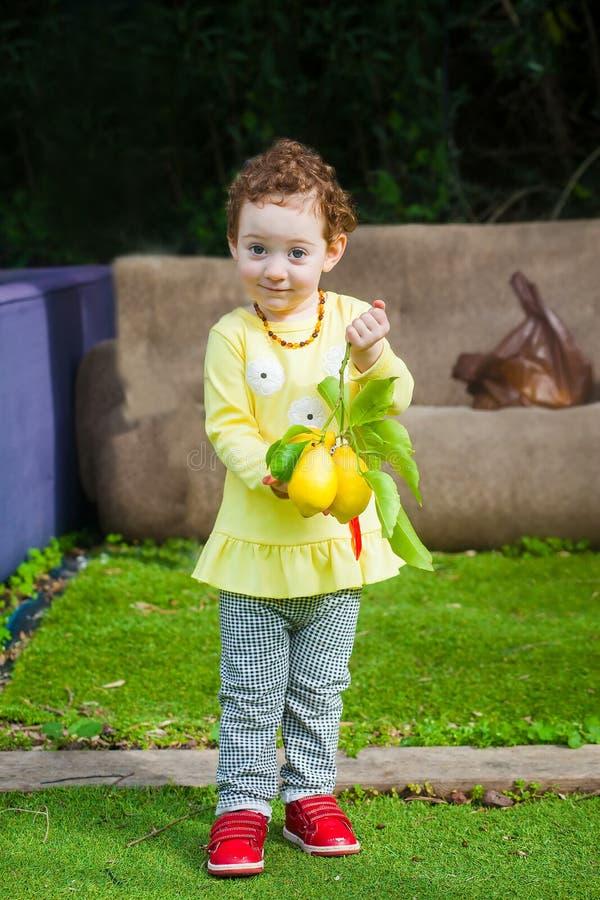 Ragazza adorabile del bambino con la frutta del limone fotografia stock libera da diritti