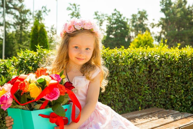 Ragazza adorabile del piccolo bambino con il mazzo dei fiori sul buon compleanno Fondo verde della natura di estate Usilo per il  fotografia stock libera da diritti
