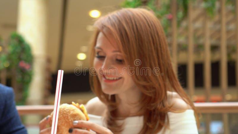 Ragazza affamata che mangia hamburger sulla corte di alimento Cheeseburger mordace della donna al fast food fotografie stock
