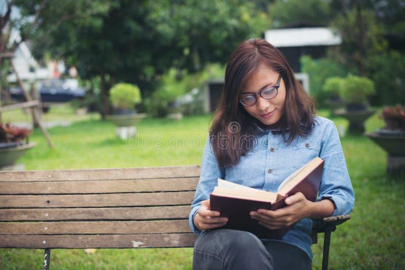 Ragazza affascinante dei pantaloni a vita bassa che si rilassa nel parco mentre libro colto, Enjo immagine stock libera da diritti