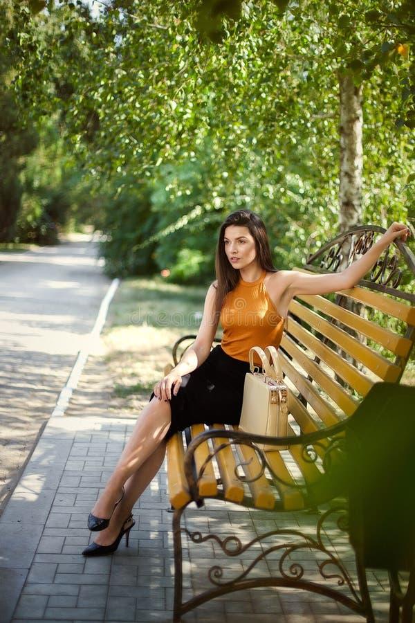Ragazza affascinante di affari con una borsa che si siede su un banco di parco fotografia stock