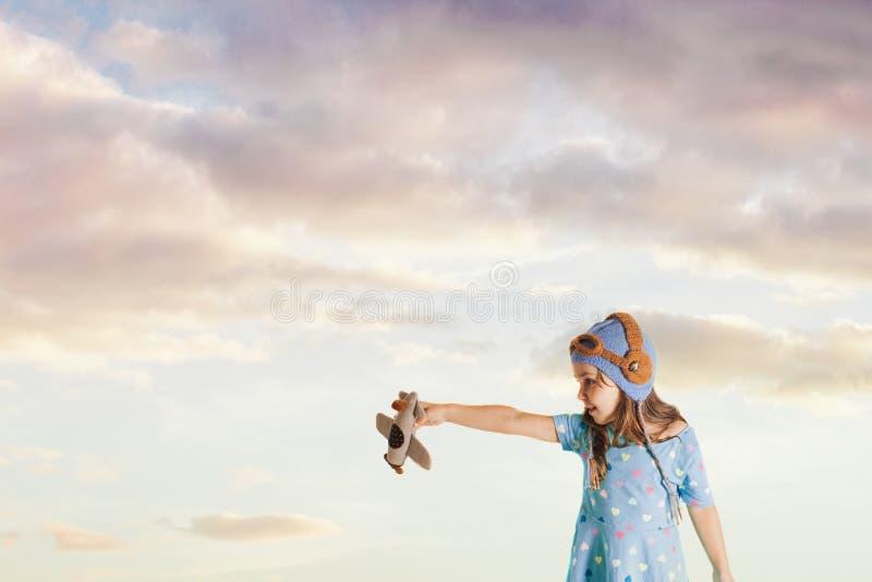 Ragazza affascinata con un aeroplano del giocattolo che immagina la sua professione futura immagini stock libere da diritti