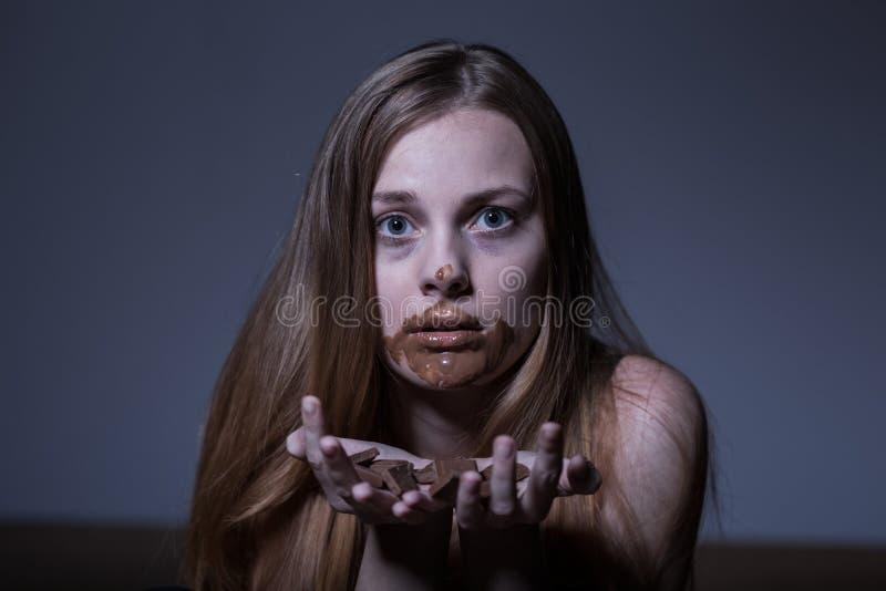 Ragazza affetta da bulimia che mangia cioccolato fotografia stock