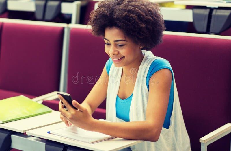 Ragazza africana dello studente con lo smartphone sulla conferenza immagine stock