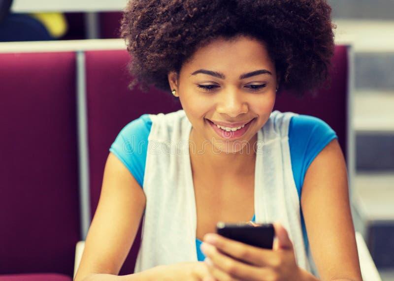 Ragazza africana dello studente con lo smartphone sulla conferenza fotografie stock