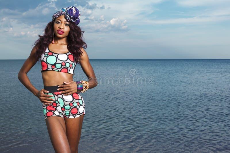 Ragazza afroamericana che si rilassa alla spiaggia fotografia stock