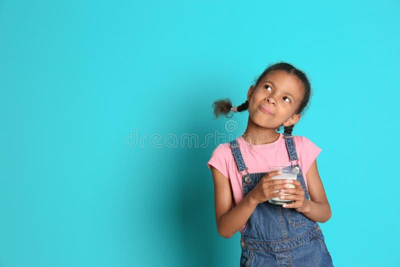 Ragazza afroamericana con bicchiere di latte sul fondo di colore fotografie stock libere da diritti