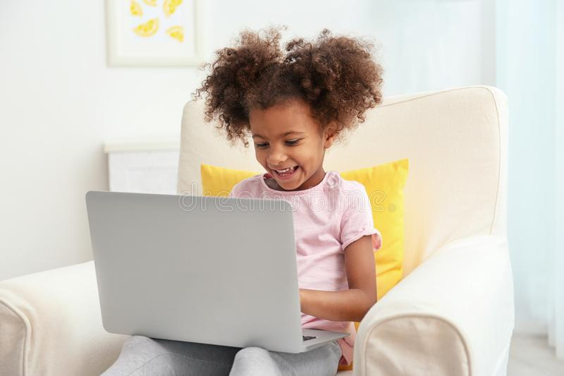 Ragazza afroamericana piccola con il computer portatile che si siede in poltrona fotografia stock libera da diritti