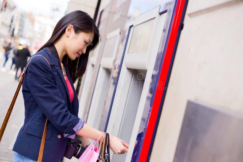 Ragazza al cash machine immagine stock