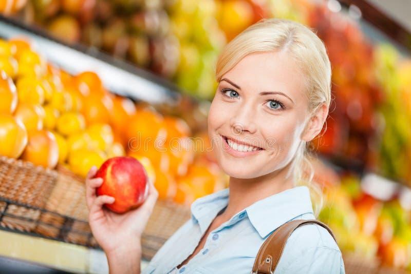 Ragazza al centro commerciale che sceglie la mela di mani di frutti immagini stock libere da diritti