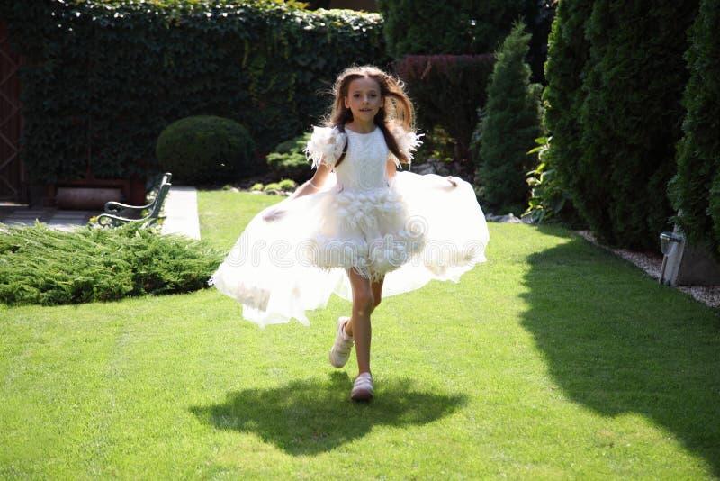 Ragazza Alice Piccoli funzionamenti di Alice lungo l'erba immagini stock