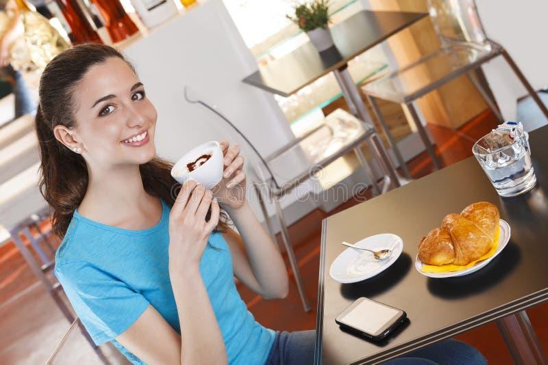 Ragazza alla barra che ha pausa caffè con cappuccino fotografie stock libere da diritti