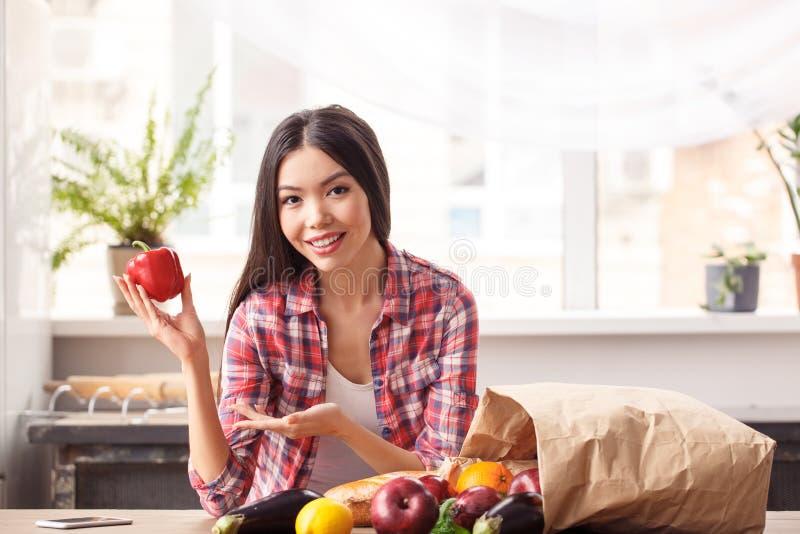 Ragazza alla condizione sana di stile di vita della cucina che si appoggia il peperone dolce di rappresentazione della tavola a s fotografia stock