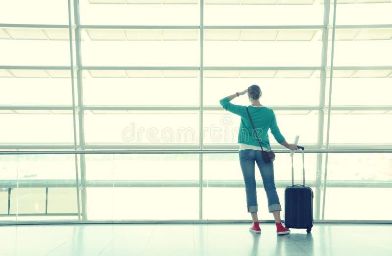 Ragazza alla finestra dell'aeroporto fotografia stock libera da diritti