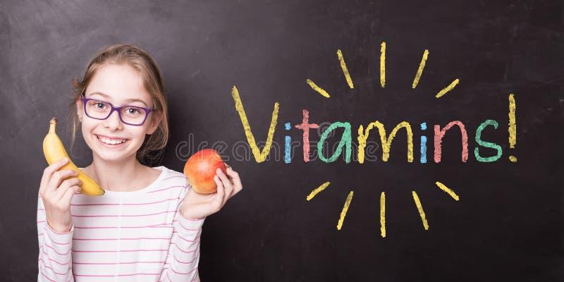 """Ragazza alla lavagna con i frutti e """"le vitamine! """"segno immagini stock"""