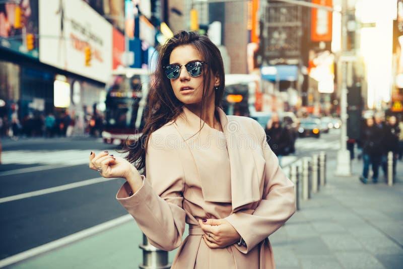 Ragazza alla moda che cammina sulla via di New York in occhiali da sole di Midtown e rivestimento d'uso di rumore metallico immagini stock