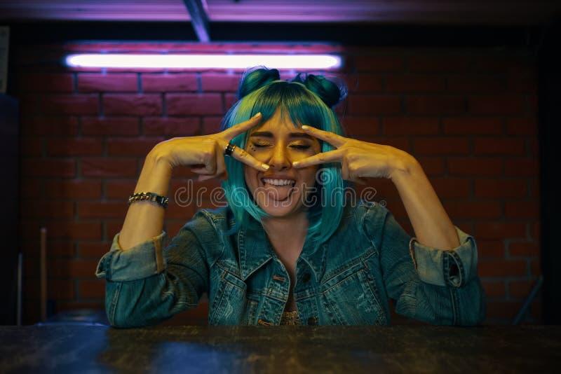 Ragazza alla moda che fa i fronti divertenti con la lingua fuori fotografie stock libere da diritti