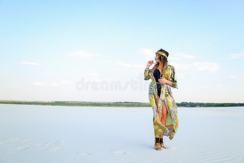 Ragazza alla moda che indossa l'abito verde della spiaggia e l'interim nero del costume da bagno immagine stock