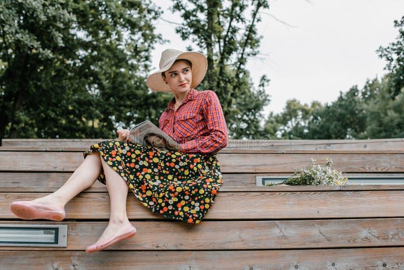 Ragazza alla moda che legge un libro Una bella donna con un cappello che si siede sulle scale di un albero Uno studente legge un  immagine stock libera da diritti