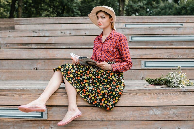 Ragazza alla moda che legge un libro Una bella donna con un cappello che si siede sulle scale di un albero Uno studente legge un  immagine stock