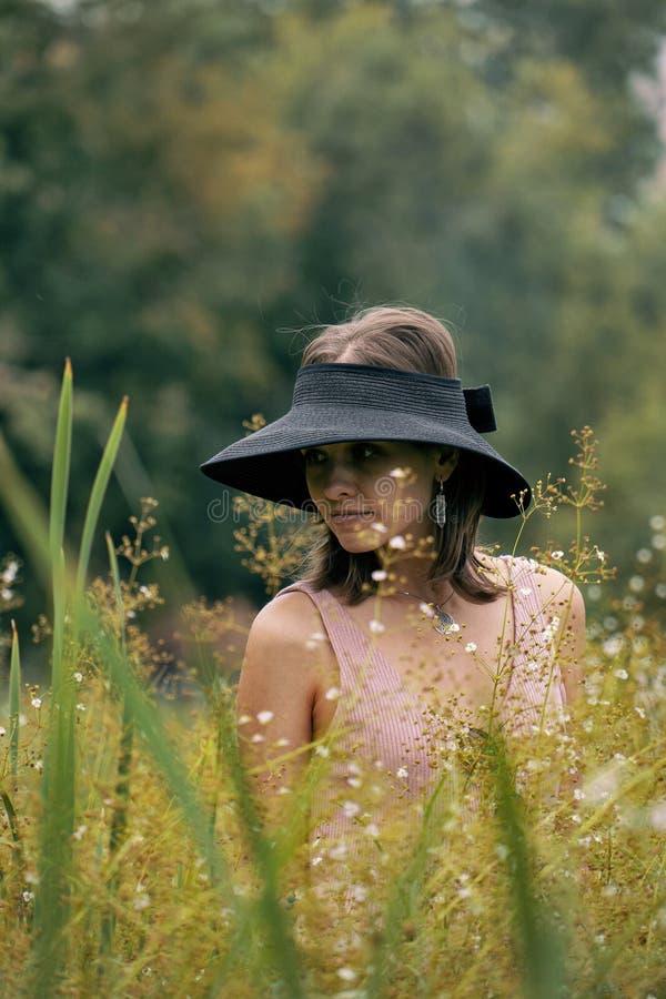 Ragazza alla moda che posa ai wildflowers Ritratto della donna calma che si rilassa fra l'erba fotografia stock