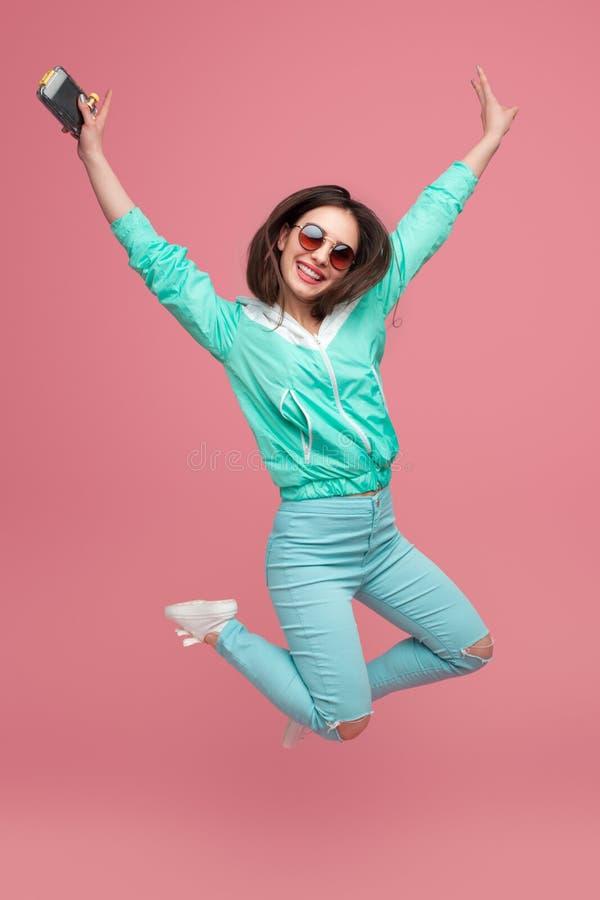 Ragazza alla moda che salta su sul rosa fotografia stock