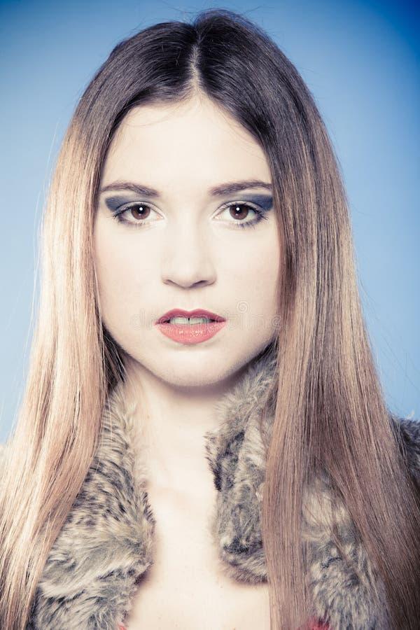 Ragazza alla moda con capelli lunghi. Giovane donna in pelliccia sul blu. fotografia stock