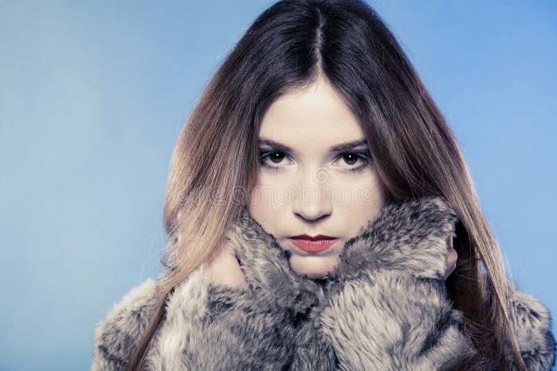 Ragazza alla moda con capelli lunghi. Giovane donna in pelliccia sul blu. fotografie stock