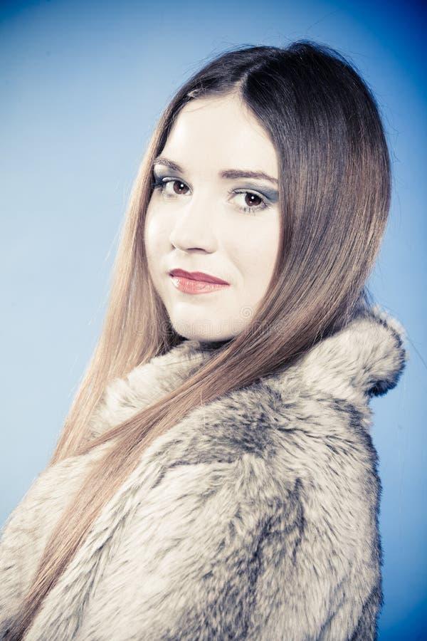 Ragazza alla moda con capelli lunghi Giovane donna in pelliccia sul blu fotografia stock libera da diritti