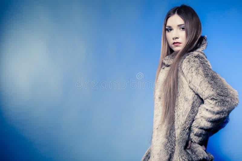 Ragazza alla moda con capelli lunghi Giovane donna in pelliccia sul blu fotografie stock