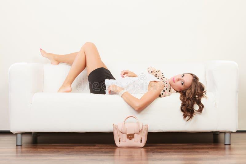 Ragazza alla moda con la borsa che si trova sul sofà immagine stock