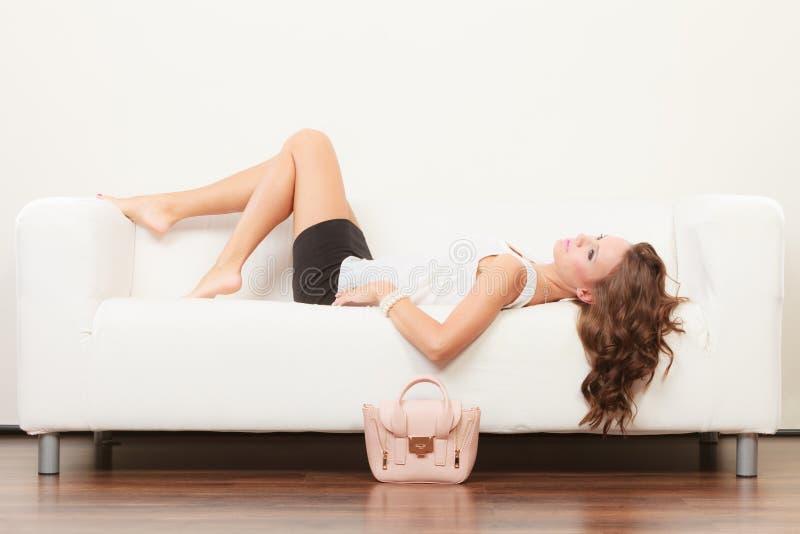 Ragazza alla moda con la borsa che si trova sul sofà immagine stock libera da diritti