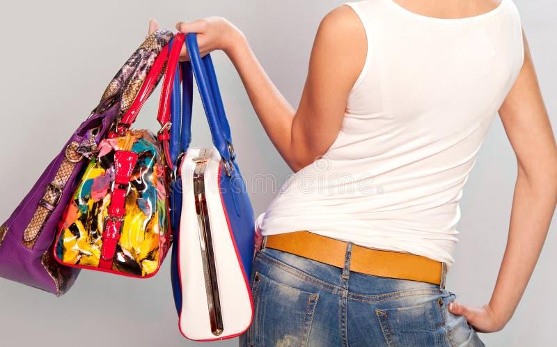 Ragazza alla moda con le borse di cuoio in mani fotografie stock libere da diritti