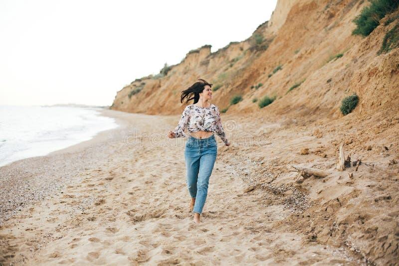 Ragazza alla moda dei pantaloni a vita bassa che corre sulla spiaggia in mare e sorridere Donna felice di boho in jeans del denim fotografie stock